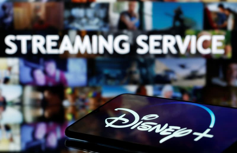 "FILE PHOTO: Smartphone with displayed ""Disney"" logo is seen in front of displayed ""Streaming service"" words in this illustration"