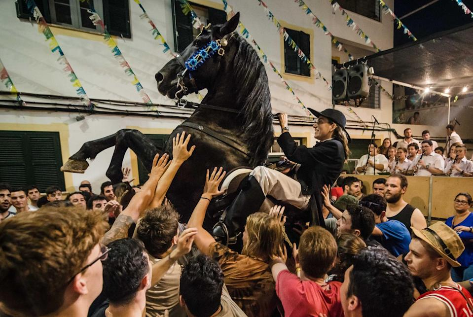 <p><span>A 'caixer' horse rider)rears up on his horse in the cheering crowd during the ' traditional 'Sant Cristofol' festival in Es Migjorn Gran. (Rex features)</span> </p>