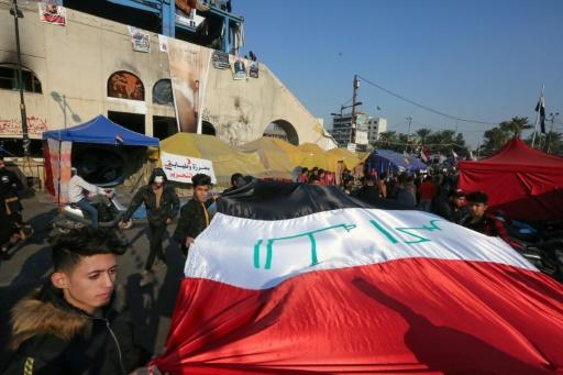 Iraqi anti-government protesters carry a large national flag during ongoing demonstrations in the capital Baghdad's Tahrir square