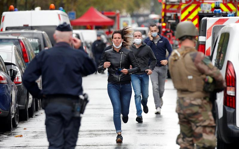 People run towards security forces at the scene - CHARLES PLATIAU/REUTERS