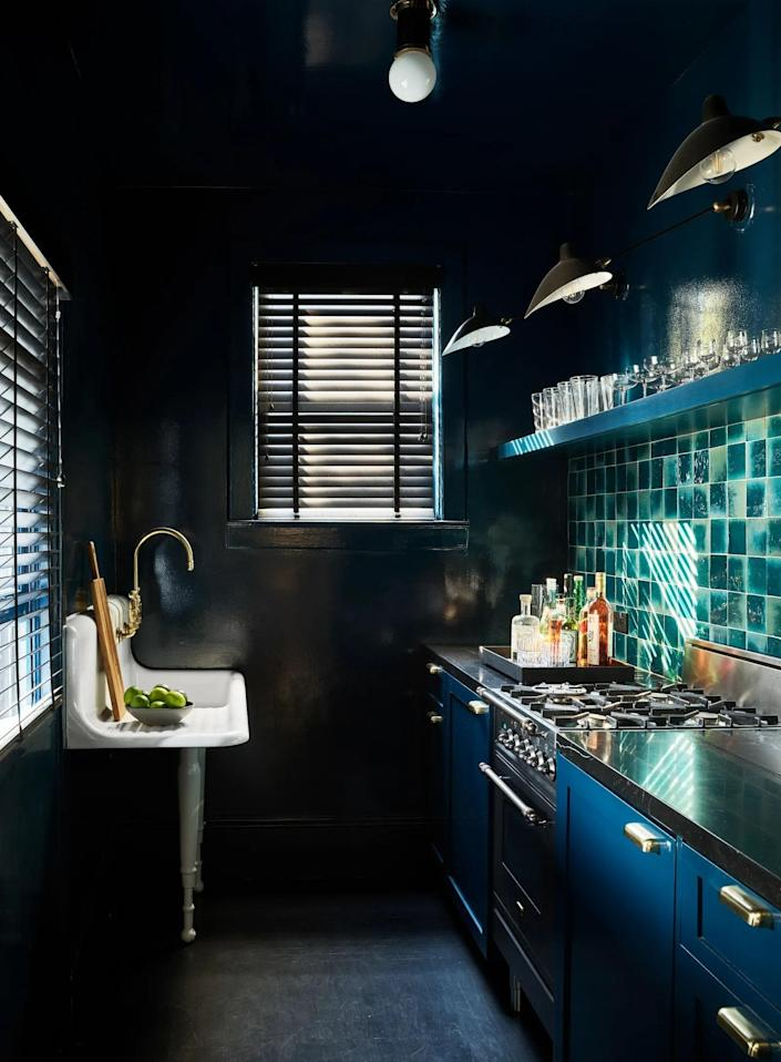 While San Francisco based designer Nicole Hollis may have turned heads for painting the exterior of her home jet black, we're prone to the moody blue she chose from Farrow & Ball for the bar.