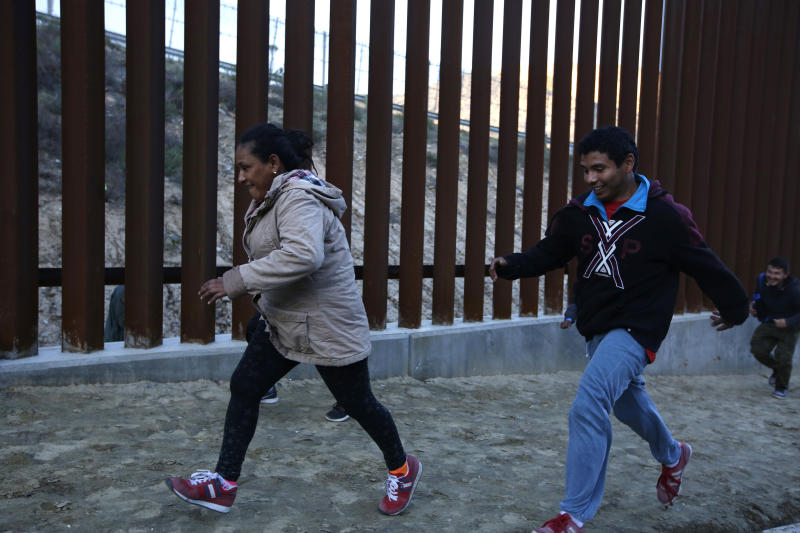 Honduran migrants run away from Border Patrol agents as they try to cross over the U.S. border wall to San Diego, California, from Tijuana, Mexico, Saturday, Dec. 15, 2018. (AP Photo/Moises Castillo)