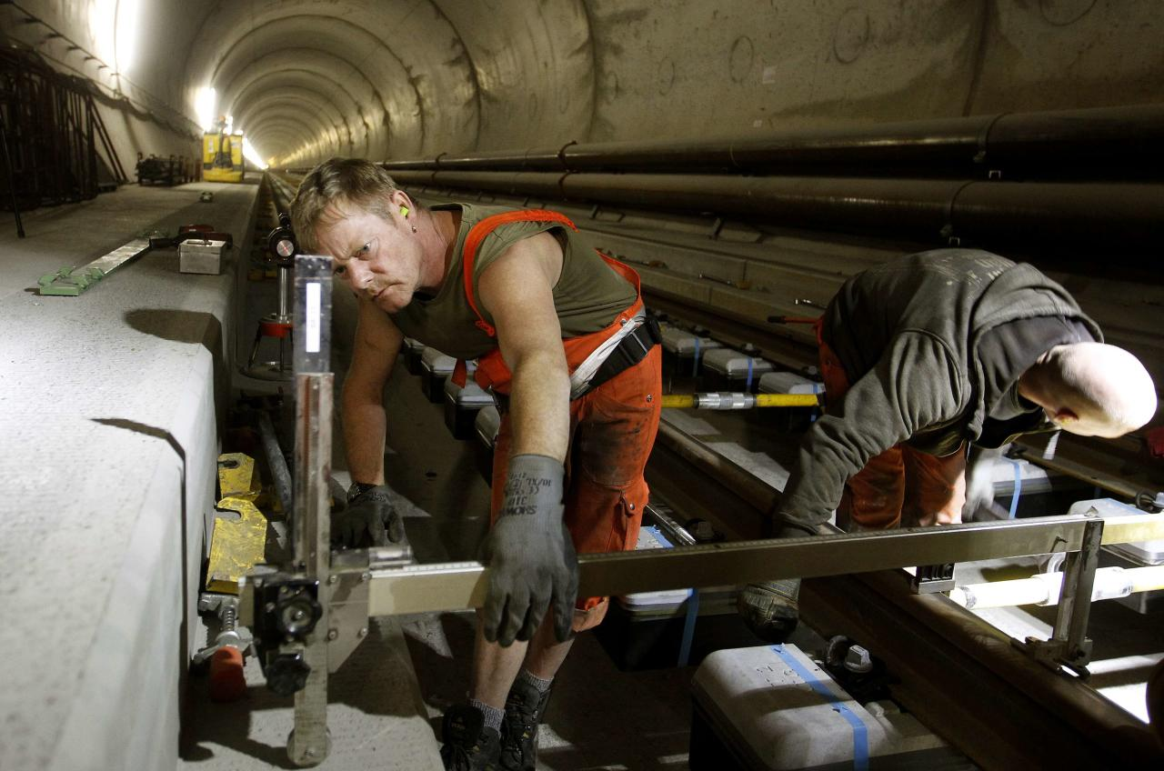 A worker uses a measuring gauge during the installation of the railway tracks in the NEAT Gotthard Base tunnel near Erstfeld May 7, 2012. Crossing the Alps, the world's longest train tunnel should become operational at the end of 2016. The project consists of two parallel single track tunnels, each of a length of 57 km (35 miles) REUTERS/Arnd Wiegmann   (SWITZERLAND - Tags: BUSINESS CONSTRUCTION EMPLOYMENT TRAVEL)