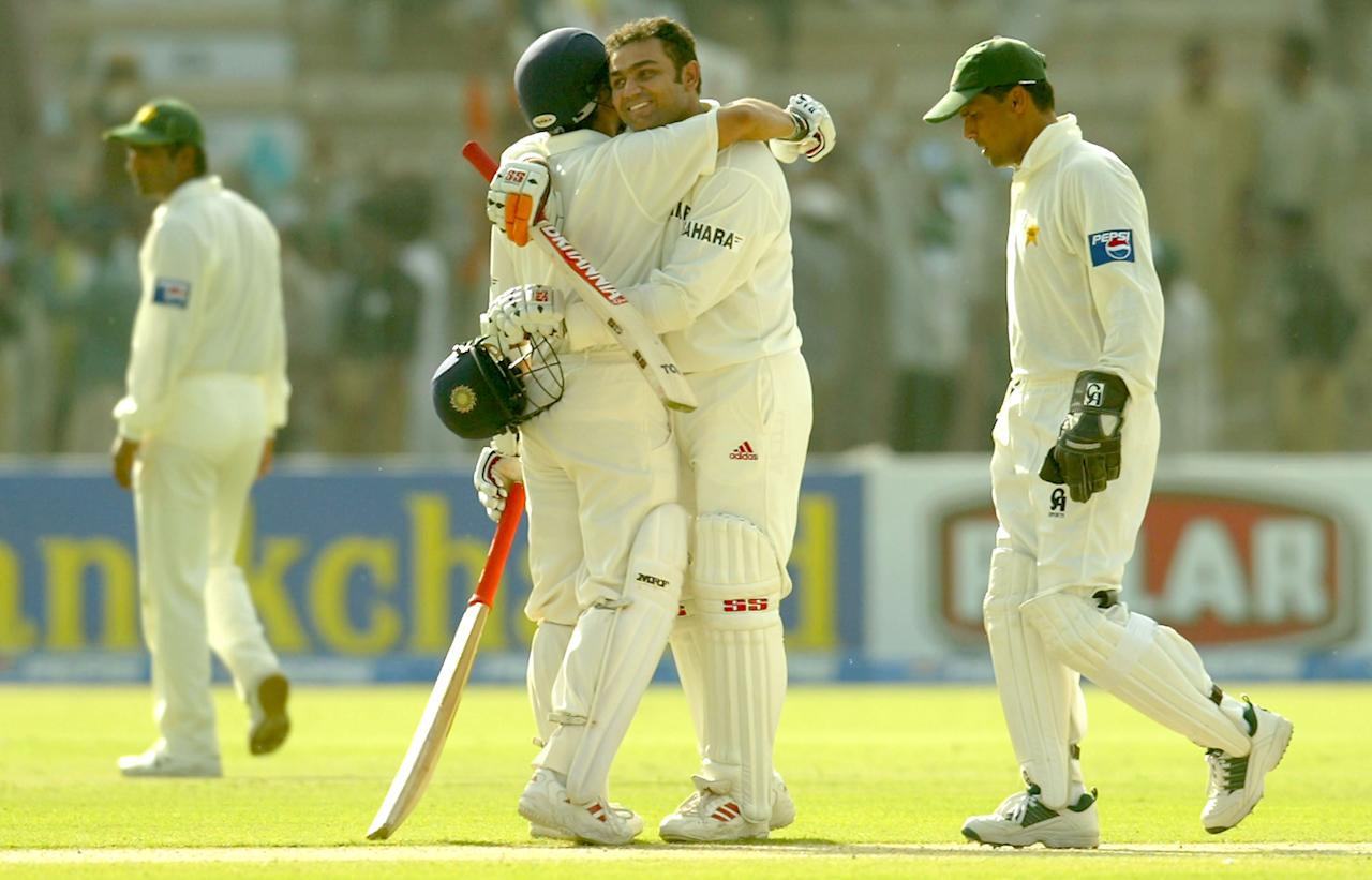 MULTAN, PAKISTAN - MARCH 28 : Virender Sehwag is hugged by Sachin Tendulkar of India after Sehwag reached his 200 during day one of the 1st Test Match between Pakistan and India at Multan Stadium on March 28, 2004 in Multan, Pakistan. (Photo by Scott Barbour/Getty Images)