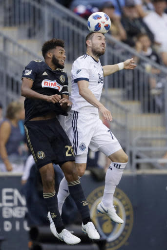 Vancouver Whitecaps' Jordon Mutch (77) and Philadelphia Union's Auston Trusty (26) leap for the ball during the second half of an MLS soccer match Saturday, June 23, 2018, in Chester, Pa. Philadelphia won 4-0. (AP Photo/Matt Slocum)