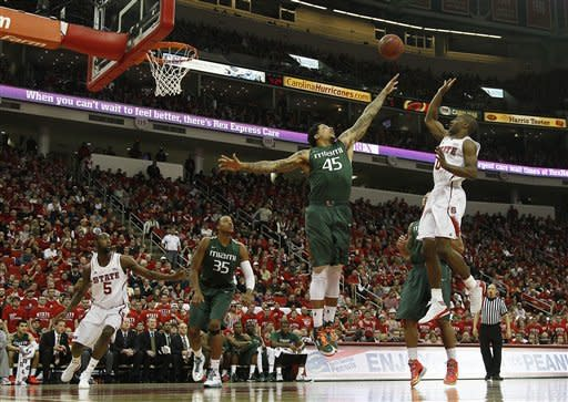 North Carolina State's Rodney Purvis (0) shoots over Miami's Julian Gamble (45) during the first half of an NCAA college basketball game in Raleigh, N.C., Saturday, Feb. 2, 2013. North Carolina State's C.J. Leslie (5) and Miami's Kenny Kadji (35) watch the play. (AP Photo/Gerry Broome)