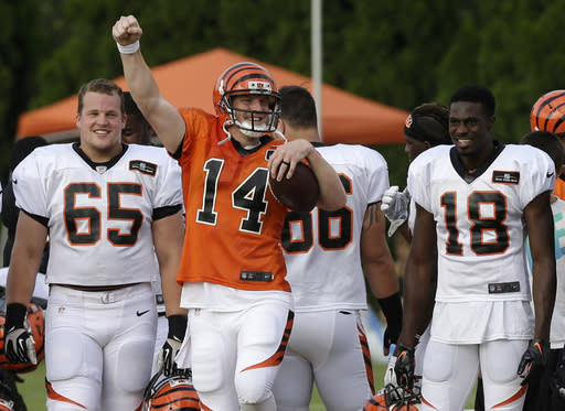 Cincinnati Bengals quarterback Andy Dalton (14) cheers from the sidelines with Clint Boling (65) and A.J. Green (18) while the kickoff squad practices at the NFL football team's training camp, Friday, Aug. 1, 2014, in Cincinnati. (AP Photo/Al Behrman)