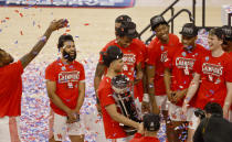 Tournament MVP Houston guard Quentin Grimes (24) holds the championship trophy and celebrates with teammates following the team's win over Cincinnati an NCAA college basketball game in the final round of the American Athletic Conference men's tournament Sunday, March 14, 2021, in Fort Worth, Texas. (AP Photo/Ron Jenkins)