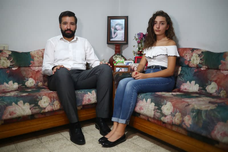 Elie Hasrouty and Tatiana Hasrouty pose for a photograph as they wait for news about their father Ghassan Hasrouty, a missing silo employee, following Tuesday's blast in Beirut's port area