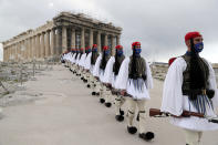 FILE - In this Thursday, March 25, 2021 file photo, members of the Presidential Guard walk in front of the Parthenon temple atop of Acropolis Hill in Athens. For Europe's battered tourism industry, chaos and confusion over travel rules and measures to contain fresh virus outbreaks are contributing to another cruel summer. Popular destination countries are grappling with surging COVID-19 variants but the patchwork and last-minute nature of the efforts as peak season gets underway threatens to derail another summer. (AP Photo/Petros Giannakouris, Pool, File)