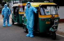 Drivers stand near auto rickshaw ambulances, prepared to transfer people suffering from COVID-19 and their relatives for free, in New Delhi