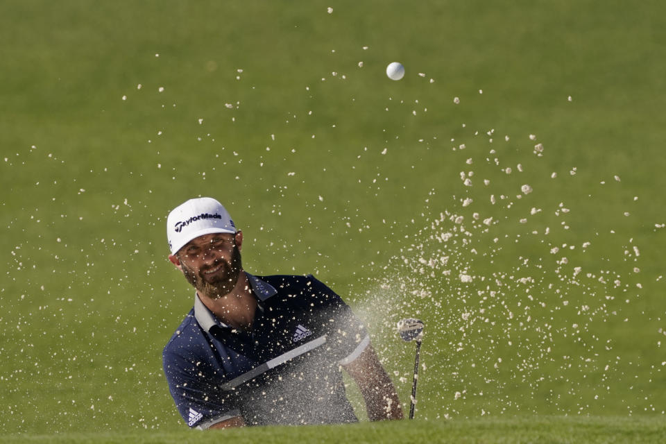 Dustin Johnson watches his bunker shot on the second hole during the second round of the Masters golf tournament Friday, Nov. 13, 2020, in Augusta, Ga. (AP Photo/Charlie Riedel)