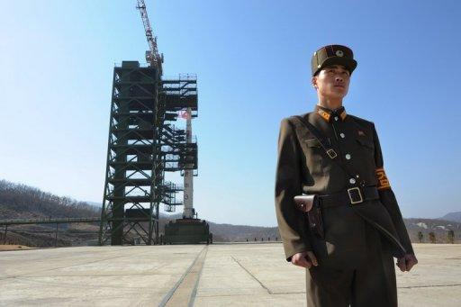 A North Korean soldier stands guard in front of the Unha-3 rocket at Tangachai -ri space center on April 8, 2012. The UN Security Council on Wednesday put three top North Korean state firms on a sanctions black list over the country's failed rocket launch