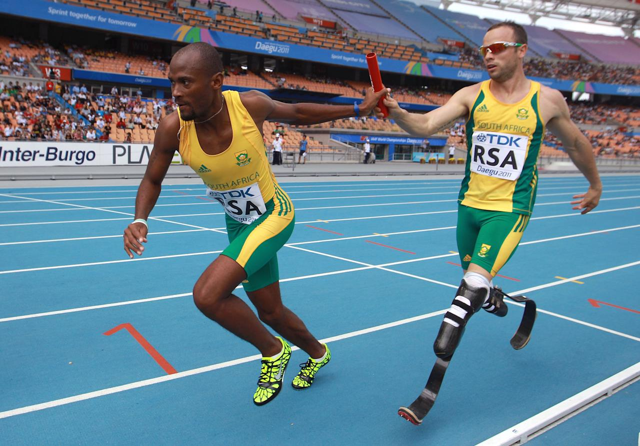 DAEGU, SOUTH KOREA - SEPTEMBER 01:  Oscar Pistorius of South Africa passes the relay baton to Ofentse Mogawane of South Africa as they compete competes in the men's 4x400 metres relay heats during day six of the 13th IAAF World Athletics Championships at the Daegu Stadium on September 1, 2011 in Daegu, South Korea.  (Photo by Alexander Hassenstein/Bongarts/Getty Images)