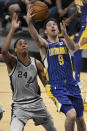 Indiana Pacers' T.J. McConnell (9) shoots next to San Antonio Spurs' Devin Vassell during the second half of an NBA basketball game Saturday, April 3, 2021, in San Antonio. (AP Photo/Darren Abate)