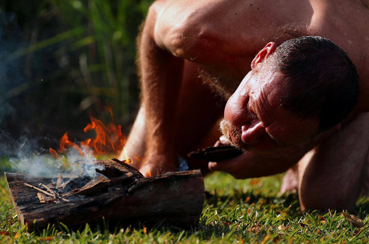 Aboriginal Terry Olsen prepares a fire before performing a smoking ceremony to mark the start of National Reconciliation Week for Aboriginal and Torres Strait Islanders in Sydney, Australia, May 28, 2018. REUTERS/David Gray