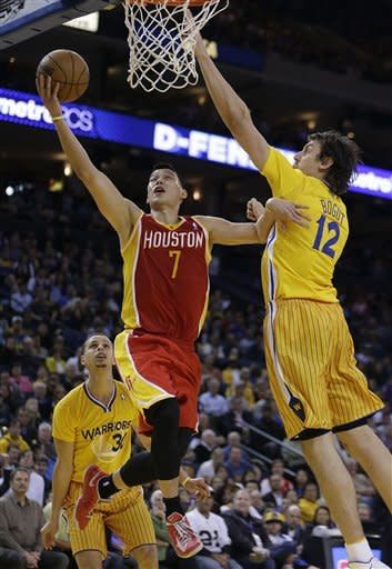 Houston Rockets' Jeremy Lin (7) lays up a shot against Golden State Warriors' Andrew Bogut (12) during the second half of an NBA basketball game Friday, March 8, 2013, in Oakland, Calif. The Rockets won 94-88. (AP Photo/Ben Margot)