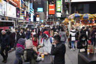 Pedestrians enjoy Times Square in New York on Christmas day, Friday, Dec. 25, 2020. The coronavirus upended Christmas traditions, but determination and imagination kept the day special for many. (AP Photo/Seth Wenig)