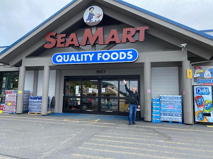Grocer Max Rule poses in front of his store, Sea Mart.
