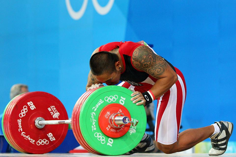 Sandow Weldemar Nasution of Indonesia kisses the weights as he competes in the men's 77kg weightlifting event during the Beijing 2008 Olympic Games. Weldemar Nasution's colorful arm tattoo features a dragon. (Photo by Phil Walter/Getty Images)