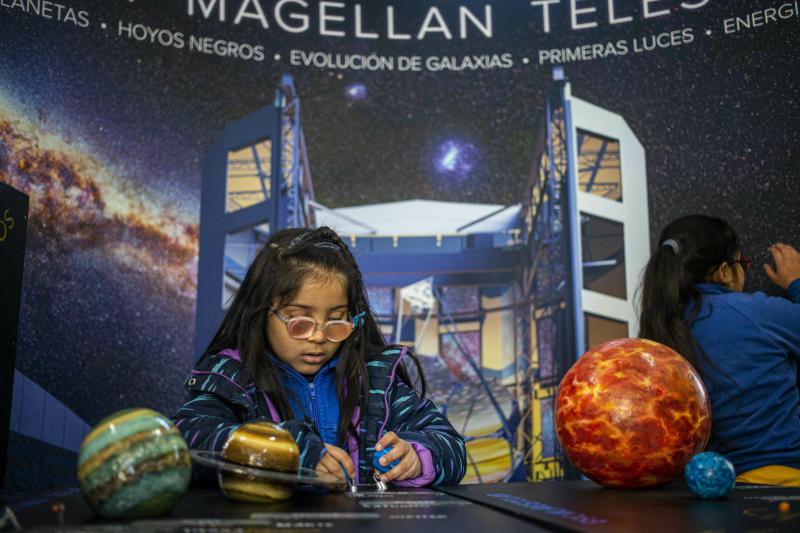 A blind child interacts with a representation of the solar system during sensorial experience with tools created by NASA and Edinburgh University to experience an eclipse, at the Helen Keller school in Santiago, Chile, Tuesday, June 25, 2019. The event comes exactly one week ahead of a total solar eclipse which is set to be fully visible in various South American countries, including Chile. (AP Photo/Esteban Felix)