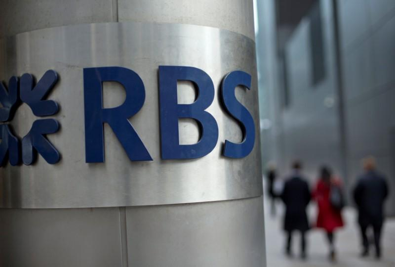 People walk past a Royal Bank of Scotland office in London