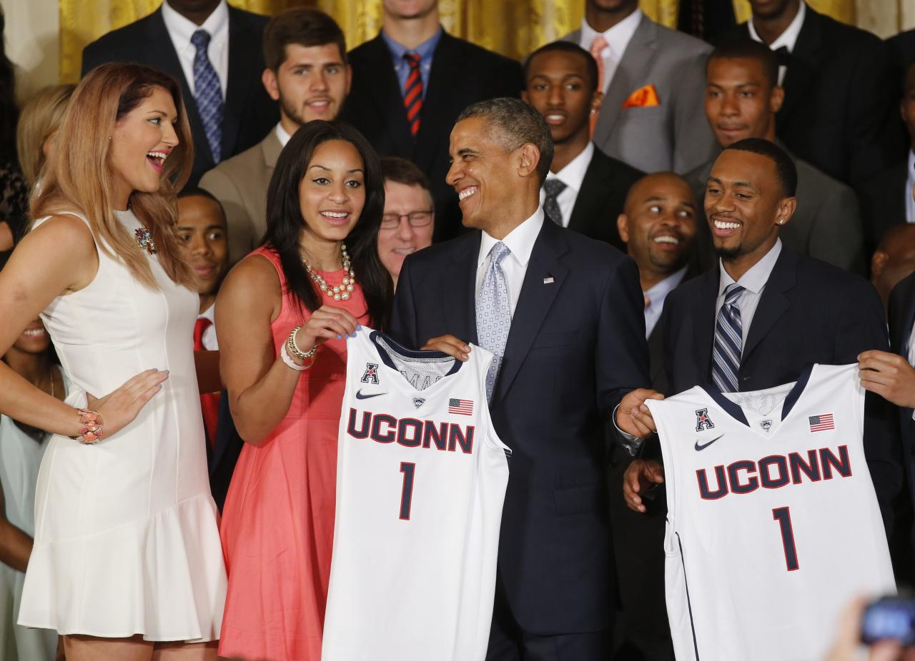 U.S. President Barack Obama laughs with UConn women's basketball stars Stefanie Dolson (L) and Bria Hartley (2nd L) as he poses with them and men's team star Ryan Boatright (R) and the jerseys of the NCAA basketball champion University of Connecticut Huskies men's and women's basketball teams in the East Room of the White House in Washington, June 9, 2014. REUTERS/Jim Bourg (UNITED STATES - Tags: POLITICS SPORT BASKETBALL)
