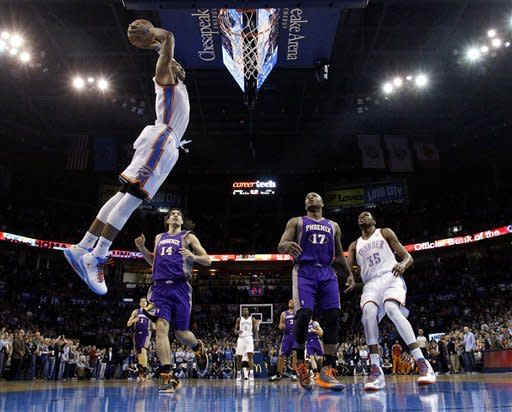 Oklahoma City Thunder guard Russell Westbrook (0) goes up for a dunk in front of Phoenix Suns forward Luis Scola (14) and forward P.J. Tucker and Thunder's Kevin Durant (35) in the first quarter of an NBA basketball game in Oklahoma City, Friday, Feb. 8, 2013. Oklahoma City won 127-96. (AP Photo/Sue Ogrocki)