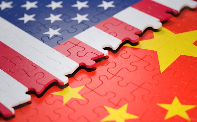 Overlapping jigsaw puzzles of the U.S. and Chinese flags.