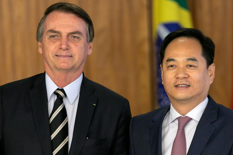 Brazilian President Jair Bolsonaro (L) poses with Chinese ambassador to Brazil, Yang Wanming, during a ceremony of presentation of new diplomats' credentials at Planalto Palace in Brasilia, on March 8, 2019. (Photo by Sergio LIMA / AFP) (Photo credit should read SERGIO LIMA/AFP via Getty Images)