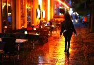 FILE PHOTO: A woman passes empty tables before the late-night curfew due to restrictions against the spread of the coronavirus disease (COVID-19)in Berlin