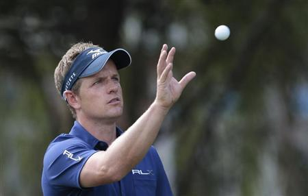 Luke Donald of Britain gets his ball back from his caddy on the fifth hole during the second round of the WGC-HSBC Champions golf tournament in Shanghai November 1, 2013. REUTERS/Aly Song