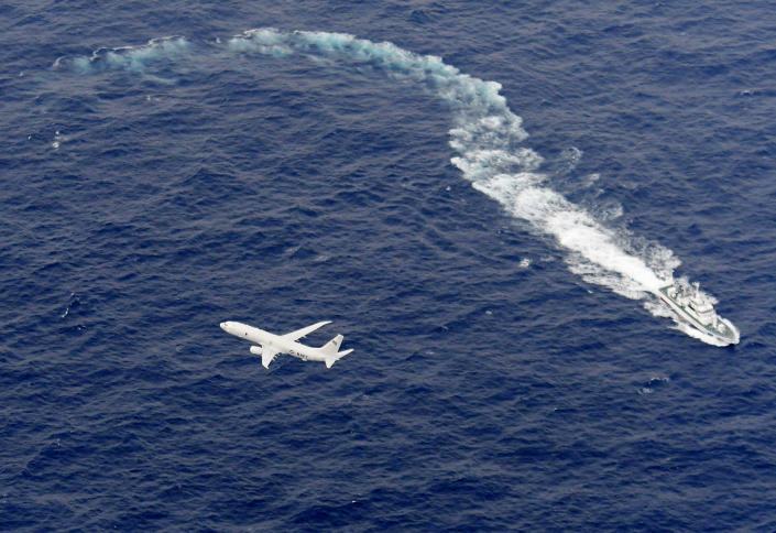 In this Dec. 6, 2018, aerial photo, Japan's Coast Guard ship, top, and U.S. military plane are seen at sea off Kochi, southwestern Japan, during the search and rescue operation for missing crew members of the U.S. Marine refueling plane and fighter jet. One of two crew members recovered after two U.S. warplanes collided and crashed off Japan's coast early Thursday is dead and five others remain missing, the U.S. military said. (Kyodo News via AP)