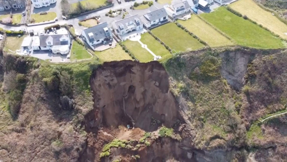 A giant landslide slid onto a beach today - only minutes after people had walked on the sand.  Large parts of clifftop gardens - and even a wooden bench - were carried onto the beach in the fall.   Police were urging people to stay away from the landslide at Nefyn near Pwllheli, North Wales, in case of more falls.  Hairdress Christian Pilling said: