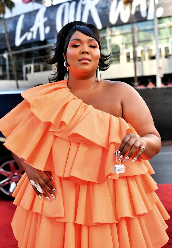 <p>Lizzo was full glam for the 2019 show, wearing a gorgeous orange one-shoulder gown.</p>