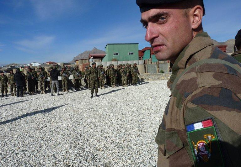 A French soldier looks on as Afghan National Army soldiers (background) stand in formation during a handover ceremony at Camp Nijrab on November 20, 2012. France has flown its last combat troops out of Afghanistan on Saturday, two years before allied nations in the 100,000-strong NATO mission led by the United States are due to recall their fighting forces
