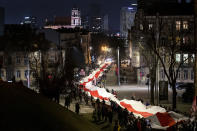 People carry a giant historical flag of Belarus during a celebration 103rd anniversary of the declaration of the Belarusian People's Respublic, in Vilnius, Lithuania, Thursday, March 25, 2021. Freedom Day is an unofficial holiday in Belarus celebrated on March 25 to commemorate the declaration of independence by the Belarusian Democratic Republic on that date in 1918.(AP Photo/Mindaugas Kulbis)