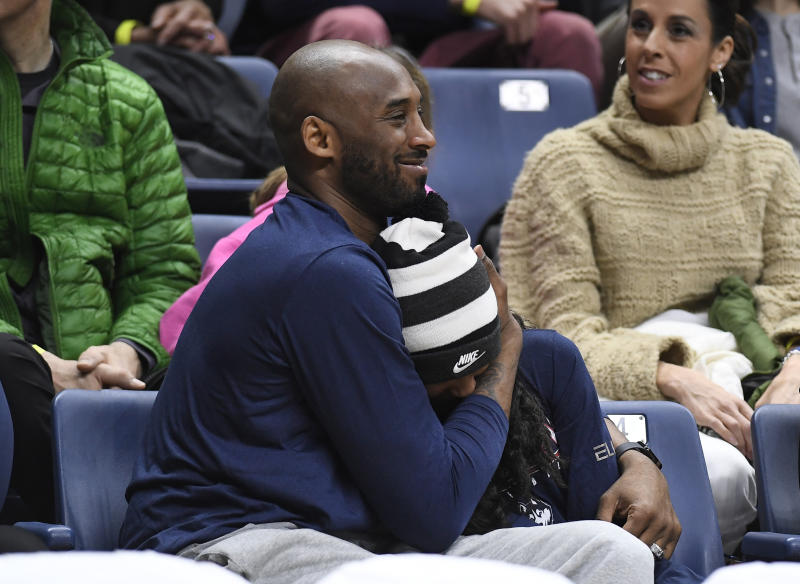 Kobe Bryant and his daughter Gianna watch the first half of an NCAA college basketball game between Connecticut and Houston, Saturday, March 2, 2019, in Storrs, Conn. (AP Photo/Jessica Hill)