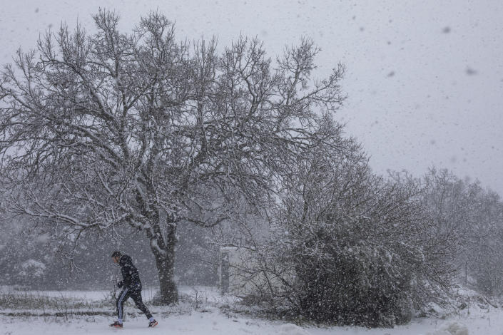 A man walks in the snow near the Quneitra border crossing between Syria and the Israeli-controlled Golan Heights Wednesday, Feb. 17, 2021. (AP Photo/Ariel Schalit)