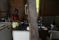 Francielle de Santana, left, cooks using the last gas canister she has, as her daughter Marcela, 8, watches a cellphone at their home in the Jardim Gramacho favela of Rio de Janeiro, Brazil, Monday, Oct. 4, 2021. Due to the rise in gas prices, Santana says she'll have to go around scraping for any recyclable material to sell to be able to afford to buy a new gas cylinder to cook. (AP Photo/Silvia Izquierdo)