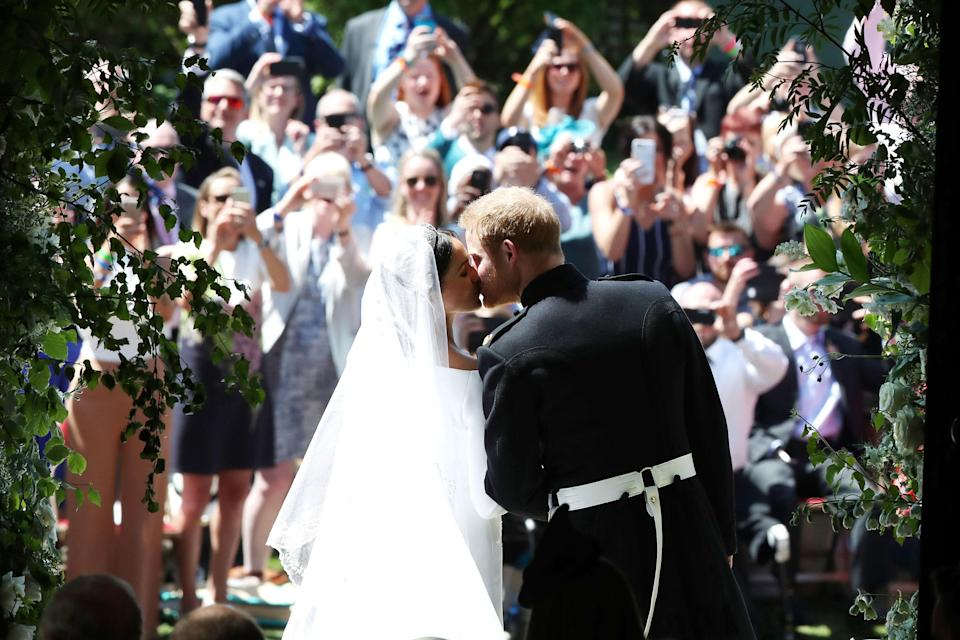 Prince Harry and Meghan Markle kiss on the steps of St George's Chapel in Windsor Castle after their wedding. [Photo: Getty]