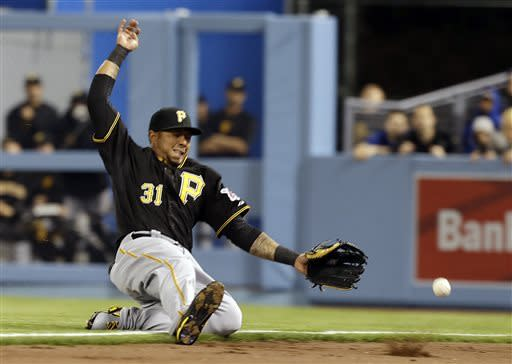 Pittsburgh Pirates right fielder Jose Tabata tries for a foul fly hit by Los Angeles Dodgers' Mark Ellis in the fifth inning of a baseball game in Los Angeles, Saturday, April 6, 2013. (AP Photo/Reed Saxon)