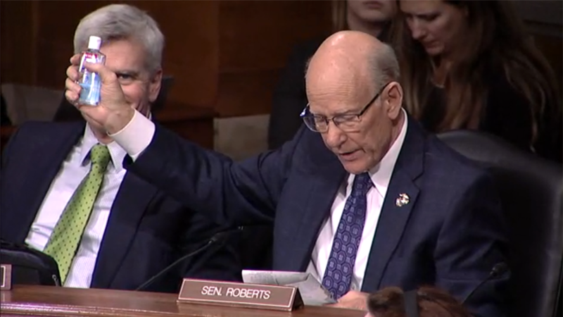 Sen. Pat Roberts hold up a bottle of Purell hand sanitizer while Sen. Bill Cassidy looks on during a Senate Health, Education, Labor and Pensions Committee Hearing on the coronavirus on Capitol Hill, Tuesday, March 3, 2020, in Washington. (Screengrab via Senate TV)
