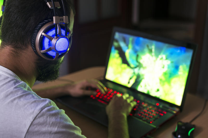 A gamer plays a game on a laptop.