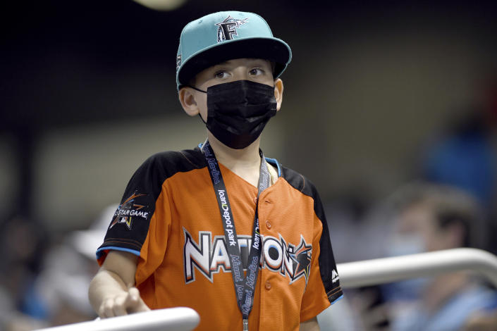 A young Miami Marlins fan watches during the seventh inning of the Marlins' baseball game against the Tampa Bay Rays, Thursday, April 1, 2021, in Miami. The Rays won 1-0. (AP Photo/Gaston De Cardenas)