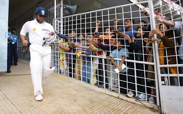 21 Dec 2001: Sachin Tendulkar of India walks out to bat in front of local admirers during the third day of the 3rd test between India and England at the Chinaswamy Stadium, Bangalore, India. DIGITAL IMAGE Mandatory Credit: Laurence Griffiths/Getty Images