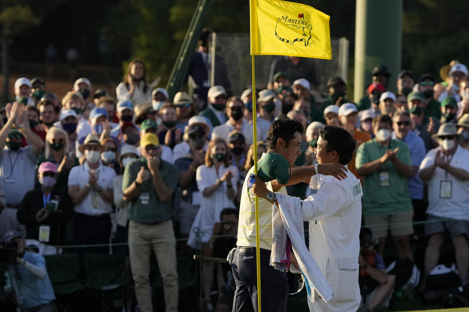 Hideki Matsuyama, of Japan, hugs his caddie Shota Hayafuji after winning the Masters golf tournament on Sunday, April 11, 2021, in Augusta, Ga. (AP Photo/Gregory Bull)