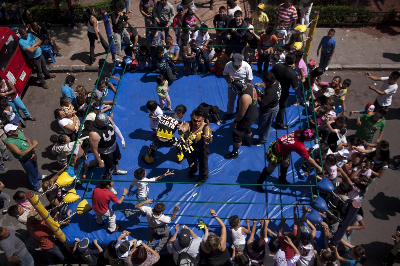 In this photo taken June 9, 2012, Mexican Lucha Libre wrestler Halloween, center, tosses sweets to children prior to his performance in a poor neighborhood in downtown Mexico City. Independent backyard shows form an underground wrestling  circuit for Mexico City's poor who lack the money to buy a 300 pesos ($22) ticket to see a professional wrestling event at one of Mexico City's big arenas. (AP Photo/Alexandre Meneghini)