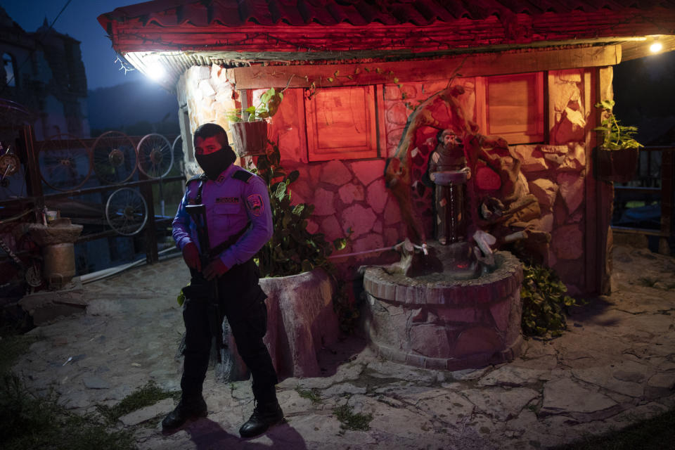 A policeman stands guard at the entrance of the mission and drug rehab center run by Friar Leopoldo Serrano, in Mission San Francisco de Asis, Honduras, Thursday, June 24, 2021. Father Serrano's message is not widely popular. He has sought protection for his mission. (AP Photo/Rodrigo Abd)