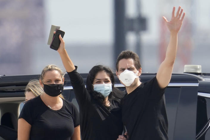 Michael Kovrig, center right, waves to media as his wife Vina Nadjibulla, centre left, and sister Ariana Botha, left, after his arrival at Pearson International Airport in Toronto, Saturday, Sept. 25, 2021. China, the U.S. and Canada completed a high-stakes prisoner swap Saturday with joyous homecomings for Kovrig and Michael Spavor, two Canadians held by China and for an executive of Chinese global communications giant Huawei Technologies charged with fraud. (Frank Gunn /The Canadian Press via AP)
